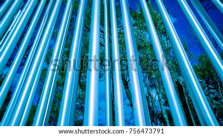 strong bright diagonal circle metal pylons against autumn forest front view, metal circle tubes texture against blue sky and green trees #756473791