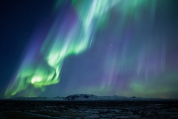 Strong bright purple green aurora noprthern lights over mountain lava plain, Thingvellir, Iceland