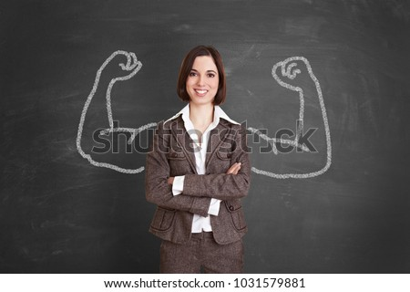 Strong businesswoman stands in front of chalkboard made of chalk