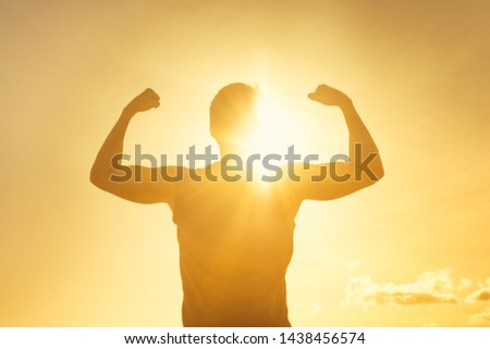 Strong confidant man flexing on sunset background.  Victory, fitness, and determination  #1438456574