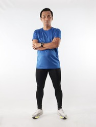 Strong confidence athletic young Asian male wearing running jersey looking at camera with crossed arms, full length studio shot portrait against white background