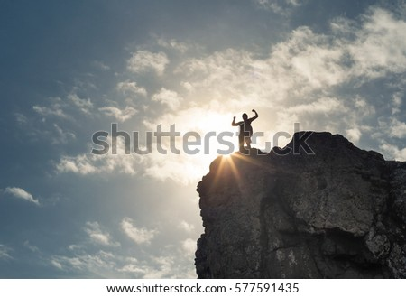 Strong confident man standing on top a mountain. Success Life goals and overcoming obstacles concept.