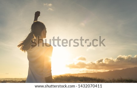 Strong, determined, confident woman with her fist up in the air facing sunset.