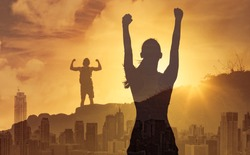 Strong determined man and woman in the city flexing, and with fist in the air. People will power, strength, and never giving up concept. Double exposure