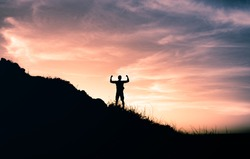 Strong determined man on mountain top flexing facing the sunrise. Adventure, determination and will power concept.