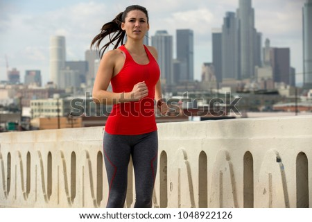 Strong determined solo jogger exercising endurance stamina and cardio downtown #1048922126