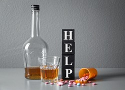 Strong drink, drugs and cubes with word HELP on table. Concept of alcoholism