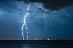 Strong electrical storm with a multitude of lightning strikes the ocean.