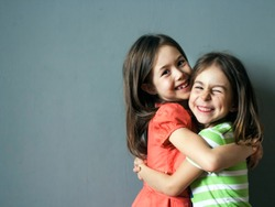 Strong embraces of two happy children. Meeting the sisters