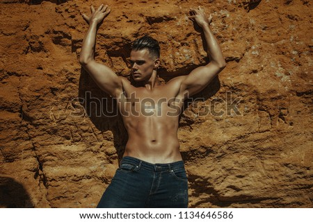 Strong face sexy sport male model in wet blue jeans in sea water on stones background