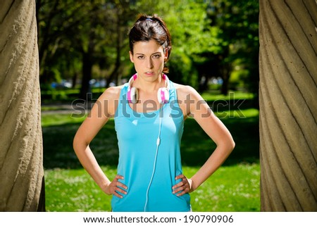 Strong fitness female athlete standing with determination and powerful attitude in city park. Woman on summer or spring workout outdoor.