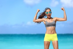 Strong fitness funny woman in neon blue wayfarer sunglasses on beach showing off muscular arms flexing biceps for fun. Fit girl in sportswear after running strength training workout winning in power.