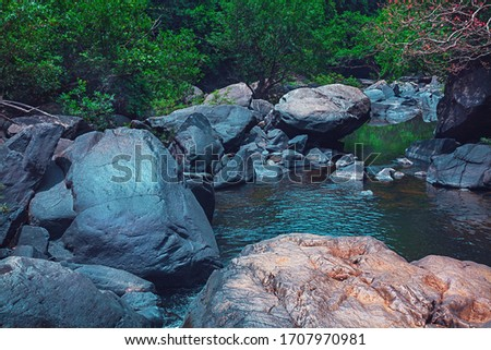 Strong flood of water rocks below.Crystal clear water, huge stones with a beautiful vegetation around. At the end forming a strong current and later a calm lake with clean transparent in India