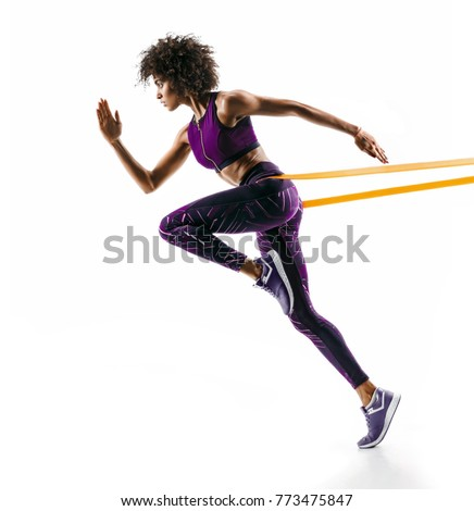 Strong girl in silhouette using a resistance band. Photo of young african girl performs fitness exercises isolated on white background. Side view #773475847