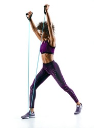Strong girl using resistance band in her exercise routine. Photo of young african girl performs fitness exercises on white background. Strength and motivation