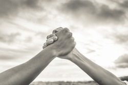 Strong hands grasping together. Unity and teamwork concept.