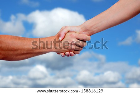 Strong handshake with a nice blue sky background