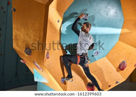 Strong handsome climber takes part in annual indoors bouldering competition for physically challenged people, trained hard with his personal instructor, wants to take first prize.