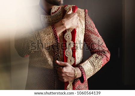 Photo of Strong handsome Indian groom holds his hands over wedding suit