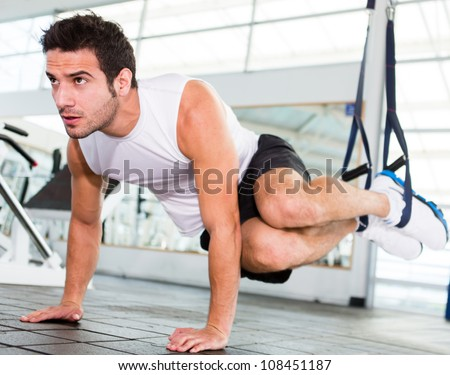 Strong handsome man exercising at the gym