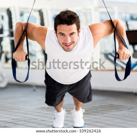 Strong handsome man exercising at the gym stock photo