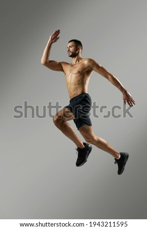 Strong handsome sportsman in sportswear warming up in the room indoors Stock photo ©