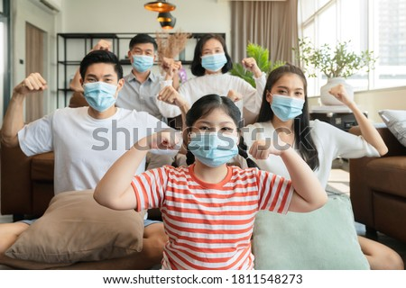 strong healthy asian family wearing surgical protective face mask stay quarantane together at home social distacing new normal lifestyle
