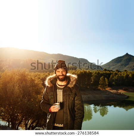 Strong hiker standing on the mountain near lake in background and resting with hot coffee. Happy multiracial smiling man outdoors. Lifestyle photo of Caucasian breaded man.