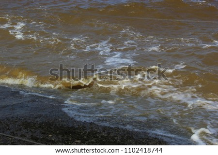 Strong, impetuous waves roll to the shore, driven by the wind  #1102418744