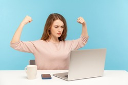 Strong independent confident woman boss raising hands showing biceps when talking on video call, looking proud, feeling power to success in business. indoor studio shot isolated on blue background