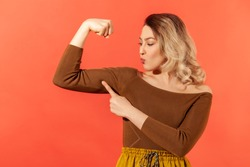Strong independent woman with blond hair showing her arm muscle and point it with finger, proud of her strength and leadership skills, emancipation. Indoor studio shot isolated on red background