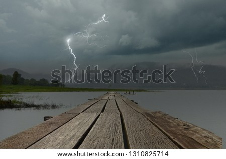 Strong lightning in black clouds over the lake