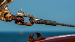 strong link of a twisted wire rope is attached to a rusty shackle of a nautical vessel offshore in front of blue blurred background