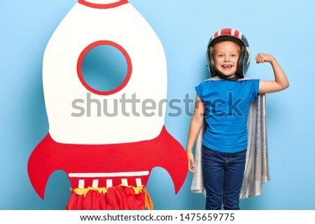Strong little child wears protective helmet and cape, shows biceps, poses near hand made rocket, ready for exploring space, wants to be astronaut, isolated on blue wall. Children and interests concept
