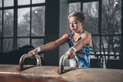 Strong. Little male gymnast training in gym, composed and active. Caucasian fit boy, athlete in sportswear practicing in exercises for strength, balance. Movement, action, motion, dynamic concept.