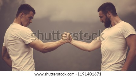 Strong male bodybuilders in white t-shirts greeting each other clasping hands together in outdoor workout over foggy mountain landscape. Rivalry, challenge, strength comparison concept #1191401671