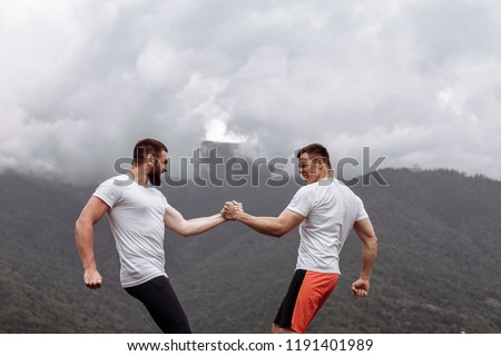 Strong male bodybuilders in white t-shirts greeting each other in arm wrestling manner, outdoor over foggy mountain landscape. Rivalry, challenge, strength comparison concept #1191401989