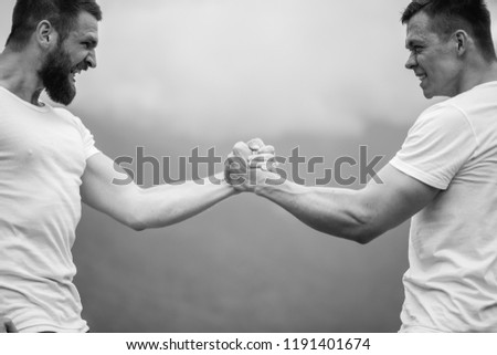 Strong male bodybuilders in white t-shirts greeting each other in wrestling manner outdoor over foggy mountain landscape. Rivalry, challenge, strength comparison concept #1191401674