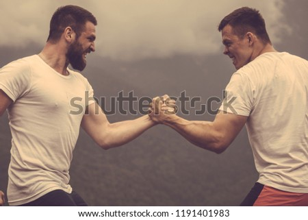 Strong male bodybuilders in white t-shirts greeting each other in wrestling manner outdoor over foggy mountain landscape. Rivalry, challenge, strength comparison concept #1191401983