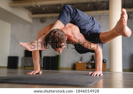 Strong male yogi standing on his hands with both feet in the air indoors Сток-фото ©