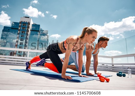Strong man and woman are doing climber exercise while staying in plank position. They are training together on sunny roof among city center. Enjoying fitness with partner on sunny day concept