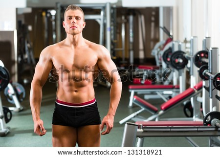 Strong man, bodybuilder posing in Gym, workout equipment in the background