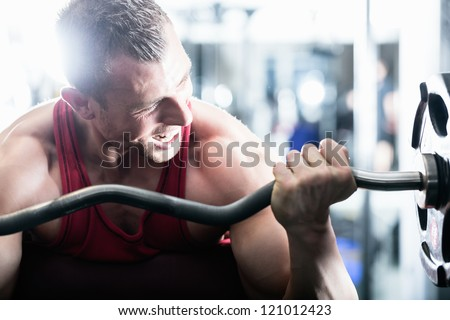 Strong man - bodybuilder with dumbbells in a gym, exercising with a barbell