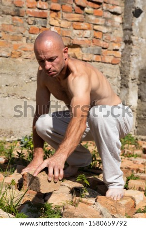 Strong Man Builds from Bricks in the Open Air. Life Style #1580659792