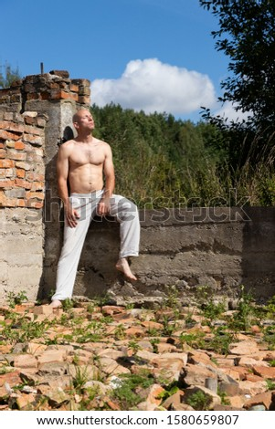 Strong Man Builds from Bricks in the Open Air. Life Style #1580659807