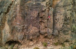 Strong man climbing a rock wall in a canyon - Climber training outdoor in a rocky spot - Travel, adrenaline and extreme dangerous sport concept - Focus on him