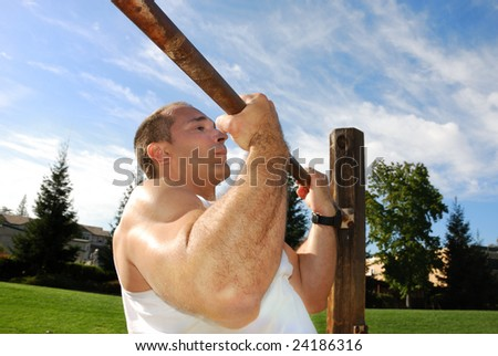 Strong Man Doing Pullups in the Park on a Sunny Day