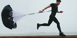 Strong man doing workout using resistance parachute outdoors. Young asian man in black sports clothing running with parachute.