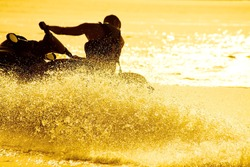 strong man drive on the jet ski above the water at sunset .silhouette. spray.