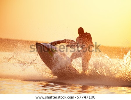 strong man drive on the jetski above the water at sunset .silluet. spray.